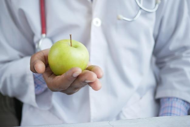 Lekarze trzymający za rękę zielone jabłko podczas lokalizacji