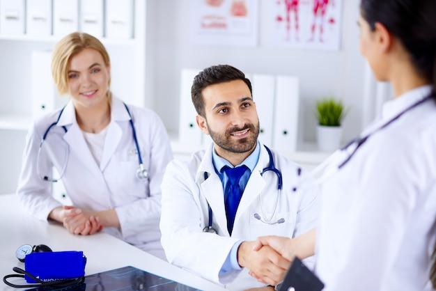 Lekarze w biurze komunikują się i podają sobie ręce.