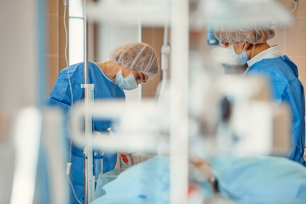 Lekarze w maskach ochronnych i fartuchach laboratoryjnych pracujący na oddziale intensywnej terapii