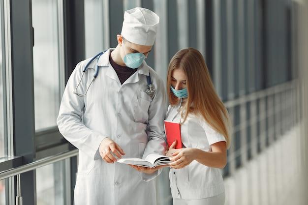 Lekarze w maskach omawiają problem na korytarzu