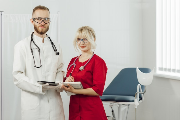 Lekarze w mundurach, mężczyzna i kobieta w gabinecie ginekologicznym.