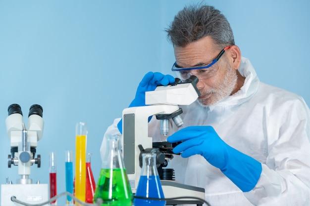 Lekarze w ochronnej odzieży ochronnej ppm noszą gumowe rękawice medyczne w celu ochrony przed chorobą coronavirus 2019 używają mikroskopu w laboratorium, coronavirus przekształcił się w globalny stan wyjątkowy.