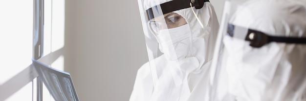 Lekarze w ochronnych kombinezonach przeciwplamowych na ekranach, patrzący na prześwietlenie płuc