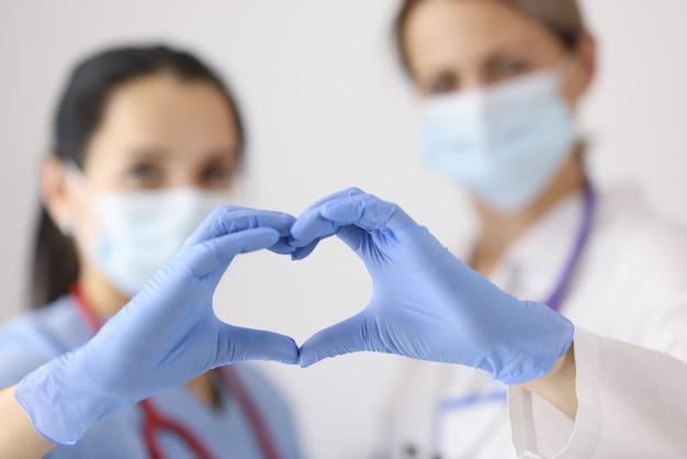Lekarze w ochronnych maskach medycznych i gumowych rękawiczkach pokazujących serce z rękami zbliżenie