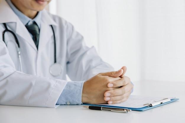 Lekarze w poradni. lekarz trzyma ręce na stole
