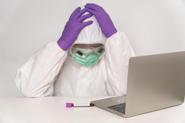 Lekarze w strojach ochronnych i maskach trzymają głowę za nieszczęśliwą i zmęczoną przyczynę przepracowania