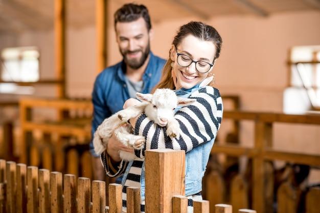 Lekarze weterynarii mężczyzna i kobieta opiekujący się małą kozą w domu w stodole