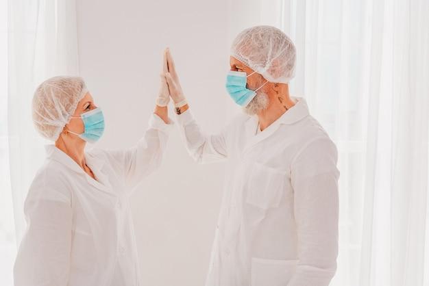 Lekarze z maską i ochraniaczem na twarz dają sobie nawzajem rękę
