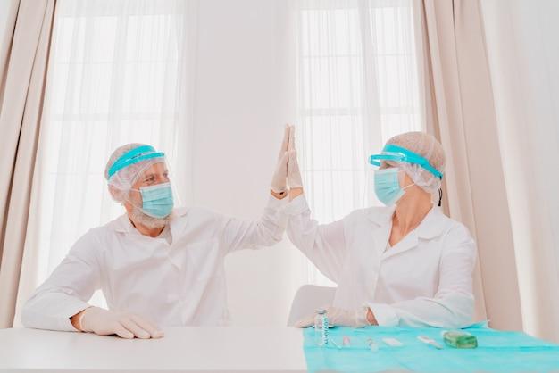 Lekarze z maską i ochraniaczem na twarz są gotowi do pracy w szpitalu