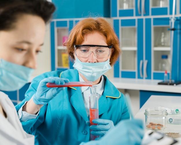 Lekarze z maskami medycznymi pracujący w laboratorium