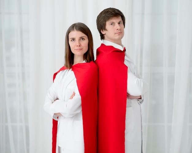 Lekarze z pelerynami pozowanie razem