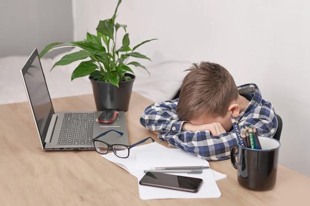 Lekcja online w domu, dystans społeczny podczas kwarantanny, izolacja, koncepcja edukacji online, uczący się w domu. chłopiec uczy się języka online, korzysta z laptopa, kształcenia na odległość. student, szkoła