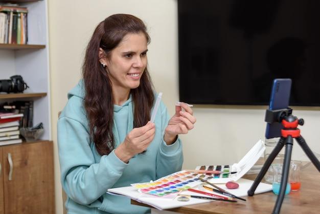 Lekcja sztuki online podczas kwarantanny. smartfon ze statywem z bliska, nauczyciel opowiada o pędzlach i rysowaniu