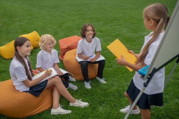 Lekcja. uczniowie siedzą razem i słuchają dziewczyny przy flipcharcie