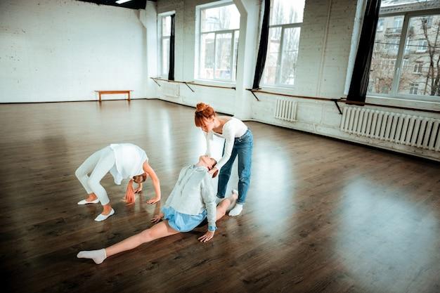 Lekcja W Szkole Baletowej. Ciemnowłosa Dziewczyna Z Pokolenia Z W Sportowym Stroju ćwicząca Rozcięte Nogi Premium Zdjęcia