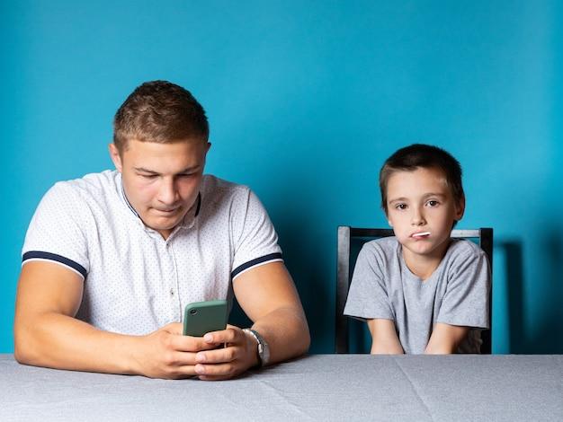 Lekcje domowe z tatą dziecka rozprasza telefon, podczas gdy syn się nudzi