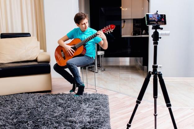 Lekcje gry na gitarze online. nastolatek chłopiec gra na gitarze i ogląda lekcje online w
