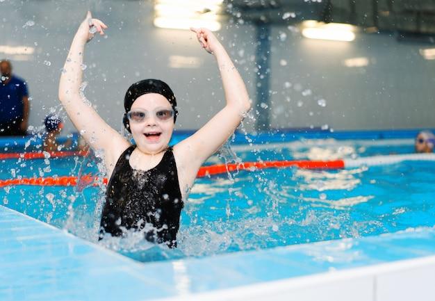 Lekcje pływania dla dzieci w basenie - piękna dziewczyna o jasnej karnacji pływa w wodzie