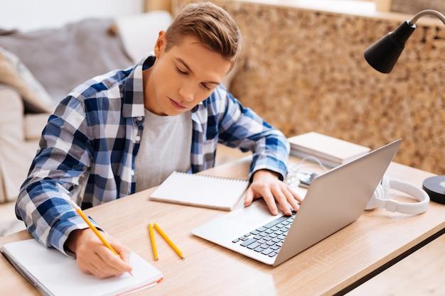 Lekcje uczenia się. atrakcyjny poważny jasnowłosy chłopak pracuje na swoim laptopie i pisze w swoim notesie, siedząc przy stole