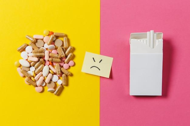 Leki białe kolorowe okrągłe tabletki ułożone abstrakcyjne białe paczki papierosów na żółtym tle koloru