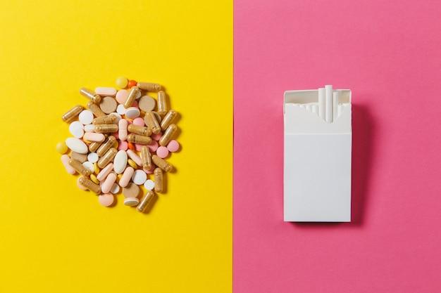 Leki białe kolorowe okrągłe tabletki ułożone abstrakcyjne paczki papierosów na żółtym tle koloru