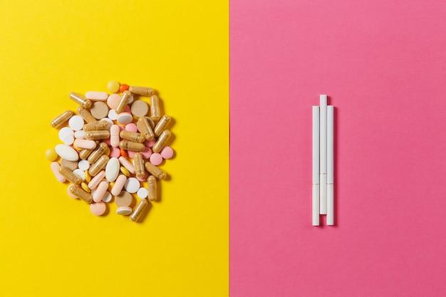 Leki białe kolorowe okrągłe tabletki ułożone abstrakcyjne trzy papierosy na żółtym tle koloru