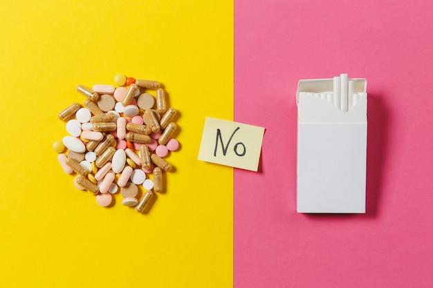 Leki białe kolorowe okrągłe tabletki ułożone streszczenie biała paczka papierosów na żółty kolor tła. tekst na arkuszu naklejki papierowej nr. wybór leczenia koncepcja zdrowego stylu życia. skopiuj miejsce.