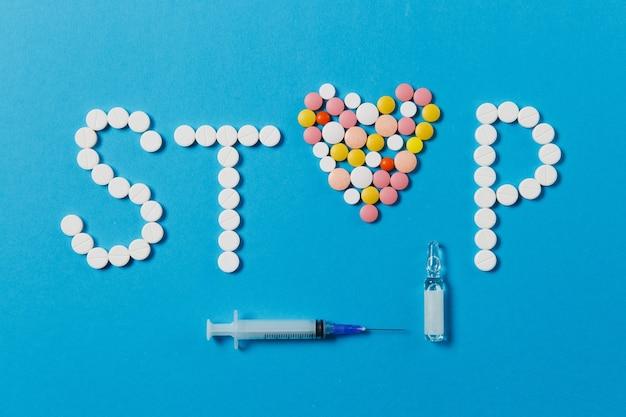 Leki białe, kolorowe okrągłe tabletki w słowie stop na białym tle na niebieskim tle. pigułki serce, ampułka, pusta igła do strzykawki. koncepcja wyboru leczenia, zdrowego stylu życia. skopiuj reklamę miejsca.