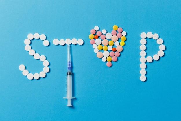 Leki białe, kolorowe okrągłe tabletki w słowie stop na białym tle na niebieskim tle. pigułki serce, pusta igła strzykawki. pojęcie zdrowia, leczenia, wyboru, zdrowego stylu życia. skopiuj reklamę miejsca.