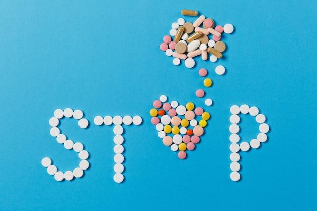 Leki białe, kolorowe okrągłe tabletki w słowie stop na białym tle na niebieskim tle. pigułki w kształcie serca, formularz, list. pojęcie zdrowia, leczenia, wyboru, zdrowego stylu życia. skopiuj reklamę miejsca.