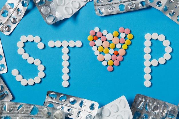 Leki białe, kolorowe okrągłe tabletki w słowie stop na białym tle na niebieskim tle. pills list, kształt serca, opakowania dookoła. pojęcie zdrowia, wybór leczenia zdrowego stylu życia. do reklamy.