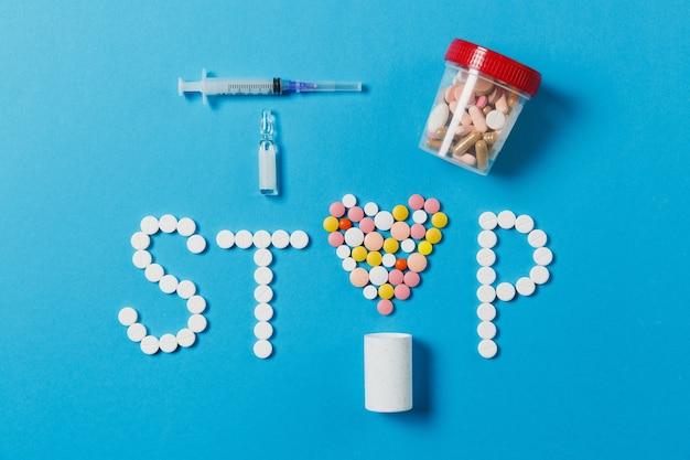 Leki białe, kolorowe okrągłe tabletki w słowie stop na białym tle na niebieskim tle. strzykawka z ampułką w kształcie serca z igłą. pojęcie zdrowia, leczenia, wyboru, zdrowego stylu życia. dla reklamowania