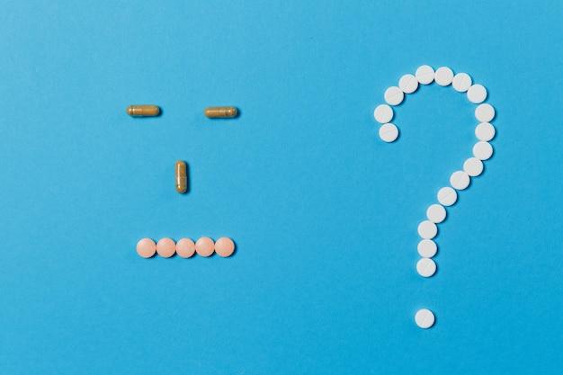 Leki białe okrągłe tabletki ułożone w kształcie znaku zapytania na niebieskim tle
