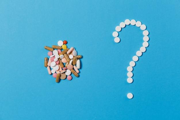 Leki białe okrągłe tabletki ułożone w kształt znaku zapytania na białym tle na niebieskim tle. kilka wielobarwnych tabletek, kolorowy znak. pojęcie zdrowia, leczenia, wyboru, zdrowego stylu życia.