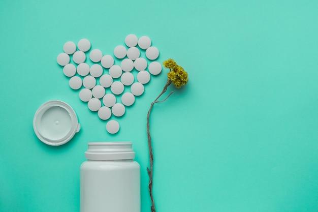 Leki białe, okrągłe tabletki w kształcie serca na białym tle na turkusowym tle.
