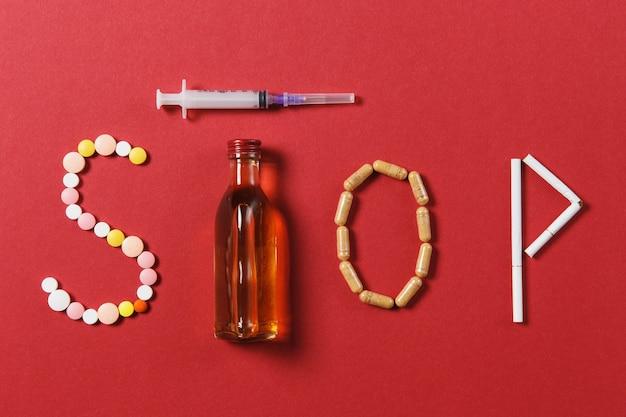 Leki białe okrągłe tabletki w słowie stop. kompozycja twórcza z komunikatem stop drinking bottle alkohol pusta strzykawka igły na czarnym tle. pojęcie wyboru, zdrowego stylu życia.