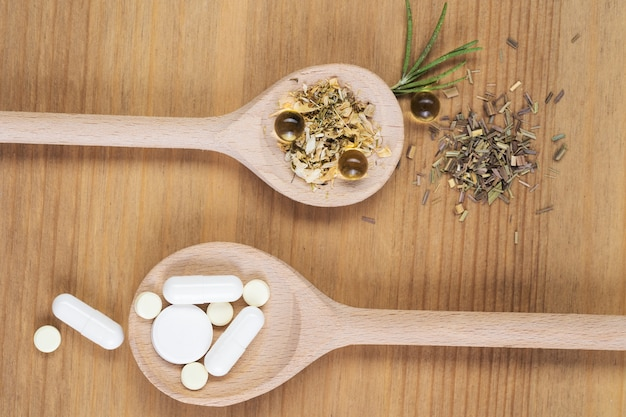 Leki homeopatyczne z tabletkami. medycyna alternatywna z ziołowymi i homeopatycznymi pigułkami na drewnianym stole