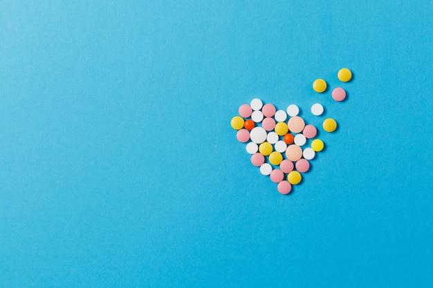 Leki kolorowe okrągłe tabletki w formie dyfuzyjnego serca na białym tle na niebieskim tle