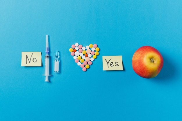 Leki kolorowe okrągłe tabletki w formie serca na białym tle na niebieskim tle. pigułki, arkusze naklejek papierowych, jabłko, tekst tak, nie, pusta igła do strzykawki. koncepcja leczenia, wybór zdrowego stylu życia.