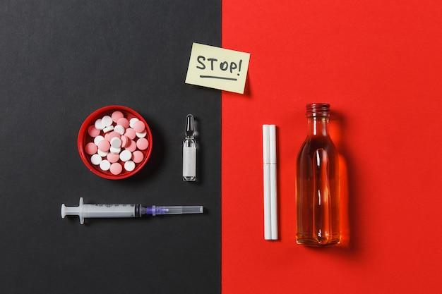 Leki kolorowe tabletki pigułki abstrakcyjne, pusta igła strzykawki, butelka alkoholu, ampułka, papierosy