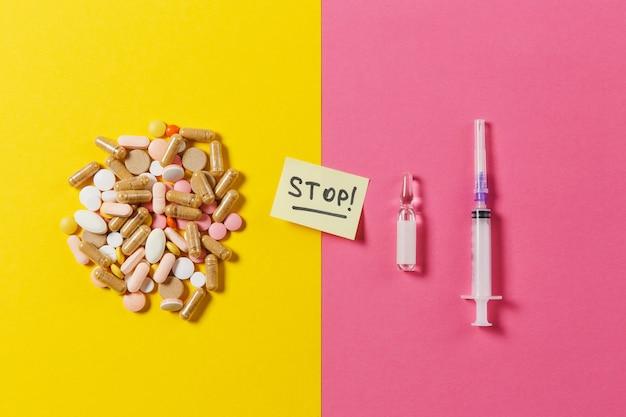 Leki kolorowe tabletki, pigułki ułożone abstrakcyjnie na żółtym różowym tle