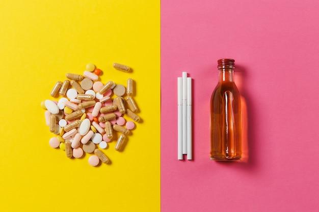 Leki kolorowe tabletki tabletki ułożone streszczenie, butelka alkoholu, koniak, whisky, trzy białe papierosy na żółty różowy kolor tła. leczenie, wybór zdrowego stylu życia. skopiuj miejsce.