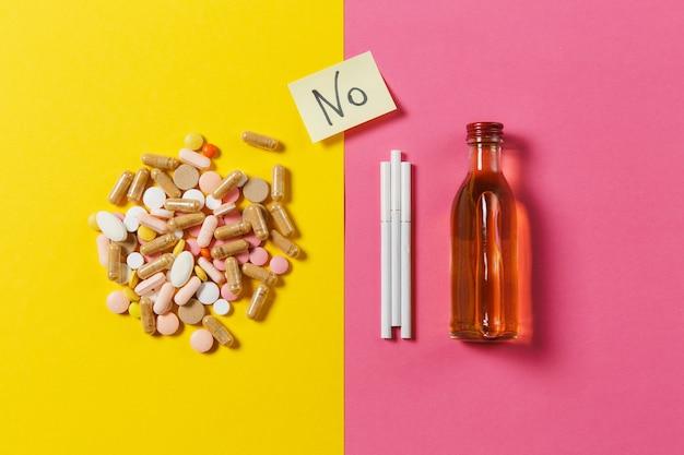 Leki kolorowe tabletki tabletki ułożone streszczenie, butelka alkoholu, papierosy na żółty różowy kolor tła. tekst na arkuszu naklejki papierowej nr. leczenie, wybór zdrowego stylu życia. skopiuj miejsce.
