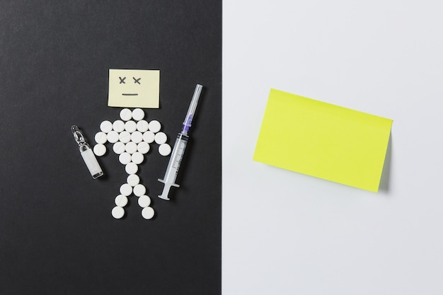 Leki okrągłe tabletki ułożone smutnego człowieka na białym czarnym tle. żółta naklejka, ampułka pusta igła do strzykawki, projekt tabletek. wybór leczenia koncepcja zdrowego stylu życia. skopiuj reklamę miejsca.