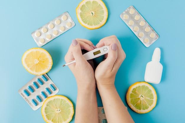 Leki, pigułki, termometr, tradycyjna medycyna do leczenia przeziębienia, grypy, ciepła na niebieskim tle.