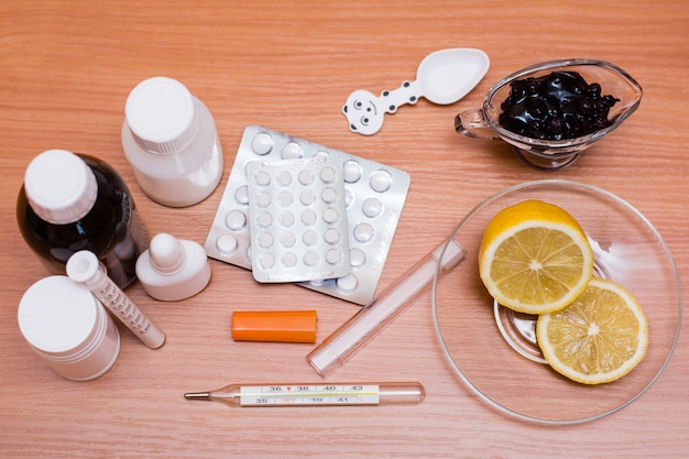 Leki, termometr, cytryna i dżem na stole. widok z góry
