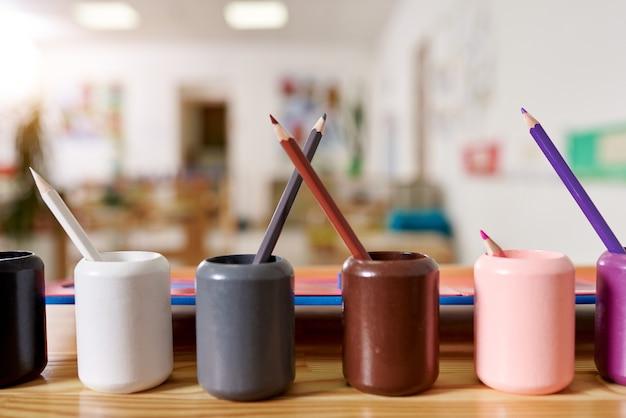 Lekka klasa w przedszkolu montessori. na pierwszym planie znajdują się kolorowe uchwyty na ołówki montessori.