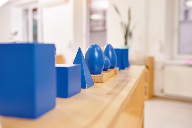 Lekka klasa w przedszkolu montessori. niebieskie geometryczne bryły montessori na pierwszym planie.