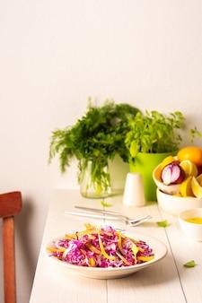Lekka letnia sałatka z czerwonej kapusty, cebuli i żółtej papryki, sałatka w talerzu na białym drewnianym stole, oliwa z oliwek z przyprawami do dressingu i bazylia z koperkiem