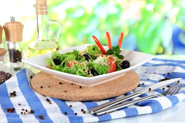 Lekka sałatka na talerzu na serwetce na rozmytej zieleni